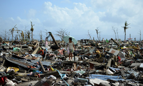 Surivor in Tacloban walks among the debris after Typhoon Haiyan