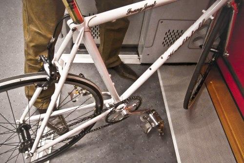 Seorang mahasiswa membawa sepeda ke kampus.